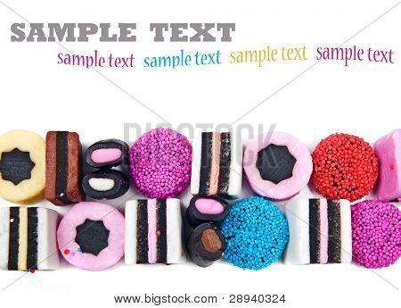 Close up of candy sweets and liquorice on a white background with space for text