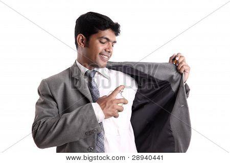 Indian business man using perfume