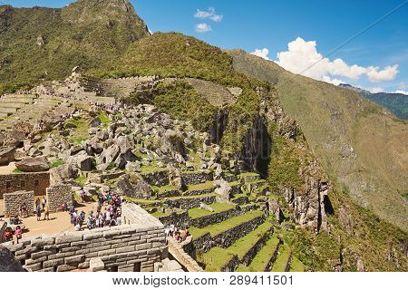 Machu Picchu, Peru - April 22, 2017: Tourist Walk On Machu Picchu Ruins On Bright Sunny Day