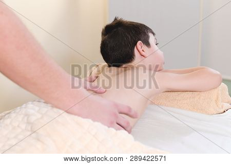 A Little Boy Relaxes From A Therapeutic Massage. Male Massage Therapist Makes A Medical Massage To T