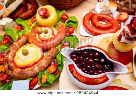 Decorated sausages with fresh vegetables and cherries are exposed on traditional sausage tournament. poster