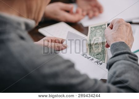 cropped view of man holding envelope with roth ira lettering and dollar banknote poster
