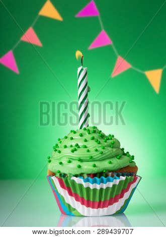 Festive Cupcake With Green Cream And A Lighted Candle On A Bright Background