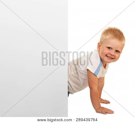 Smiling Little Boy In Front Of A Blank Banner Isolated On White Background