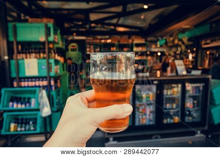poster of City market with beer store and glass in hand of drinker. Many stores with drinks and delicacy food inside market of Copenhagen, Denmark.