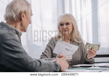 senior couple holding envelope with roth ira lettering and dollar banknote at home poster