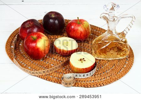 Apple Vinegar And Apples. Fresh Apples, Apple Vinegar, Measuring Tape And A Bottle  On White Wooden