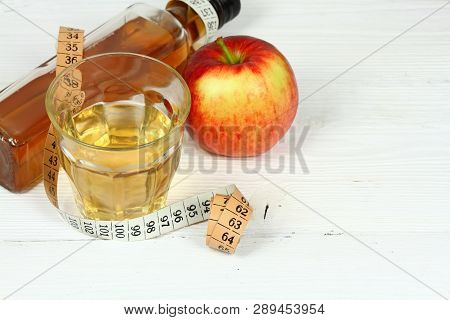 Apple Vinegar And Apples. Fresh Apple, Apple Vinegar, Measuring Tape And Glass On White Wooden Table