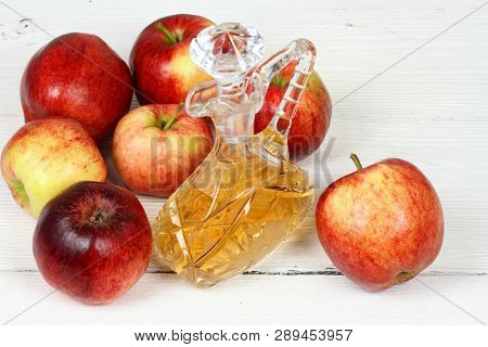 Apple Vinegar And Apples. Fresh Apples, Apple Vinegar And A Bottle  On White Wooden Table