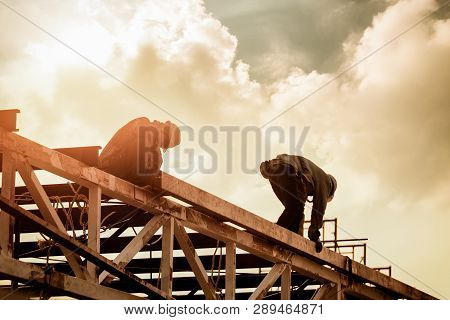 Welding Steel Worker Action In The Factory Building. Roof Steel Structure Fabrication Jobs.