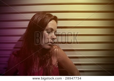 Young Pensive Woman Leans Against Wall