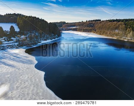 Aerial View Of The Partially Frozen Lingese Dam (lingesetalsperre)near Marienheide In Winter.