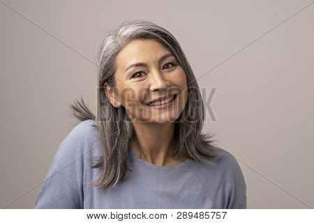 Attractive Senior Asian Woman Broadly Smiles At Camera. Beautiful Grey-haired Woman Lifts Her Right