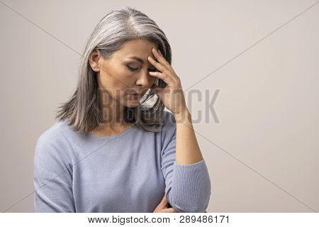 Serious Middle-aged Woman Touches Her Forehead While Thinking About Something. Upset Asian Woman Wit