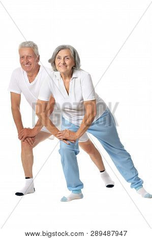 Cute Senior Couple Exercising On White Background