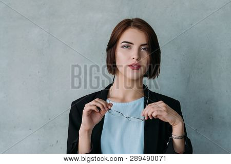 Ambitious Corporate Intern. Young Attractive Business Woman With Glasses. Copy Space On Grey Backgro