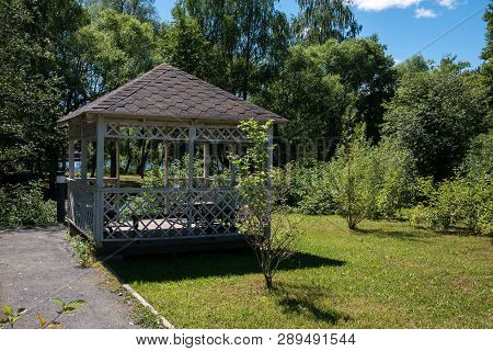 Wooden Summerhouse On Lawn Among Lush Green Trees On Bright Sunny Summer Day