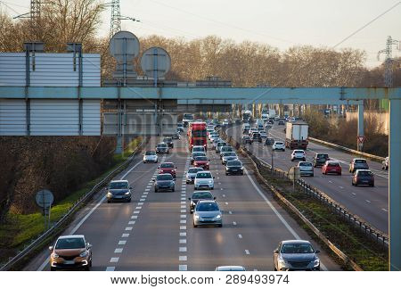 Numerous cars driving on highway in a traffic jam. Vehicle junction on the asphalt road, urban outdoor background. City streets congestion during rush hours, infrastructure and transportation concept. poster