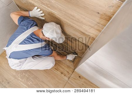 Caucasian Worker Grouting And Sealing Shower Cabin Using Silicone And Grout. Bathroom Remodeling.