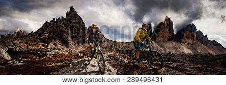 Couple bike riders on electric bike, e-mountainbike rides up mountain trail. Woman and Man riding on e-bike in Dolomites mountains landscape. Cycling e-mtb enduro trail track. Outdoor sport
