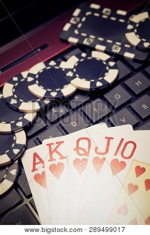 Casino chips and cards stacking on a laptop.