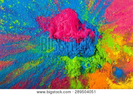 poster of Abstract colorful Happy Holi background. Color vibrant powder on wood. Dust colored splash texture. Flat lay holi paint decoration