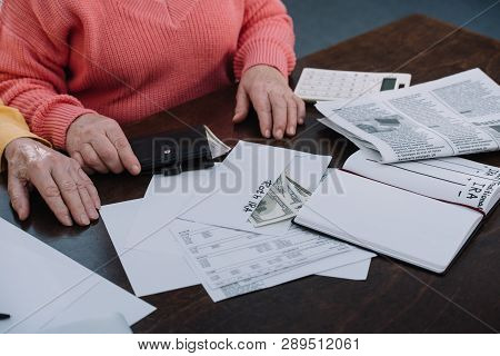 cropped view of senior couple sitting at table with paperwork, envelope with roth ira lettering, money and notebook poster
