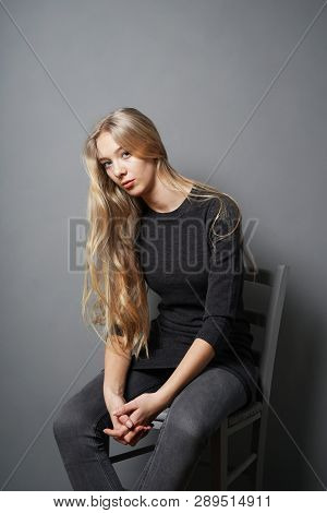 Teenage Girl Slouching On Chair - Gray Background With Copy Space