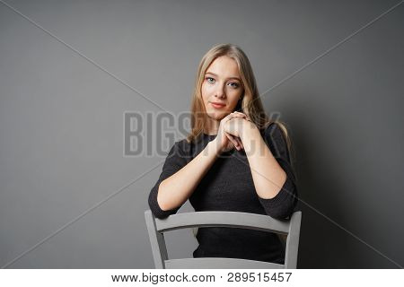 Serene Young Woman Sitting Astride On Chair - Gray Background With Copy Space