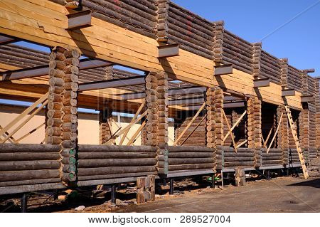 New Wooden Blockhouse. Construction Of A House Or Dwelling. Walls Of Round Treated Pine Trunks. The