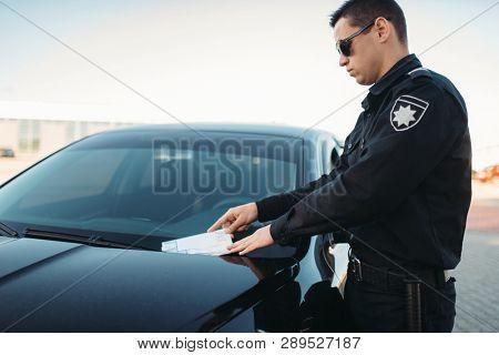 Male policeman in uniform writes a fine on road