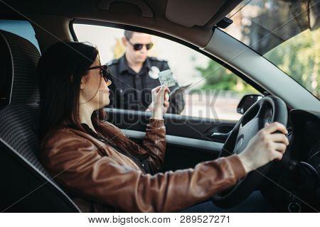 Male cop in uniform writes a fine to female driver