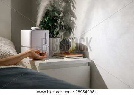 Hand Turn On Aroma Oil Diffuser On The Bedside Table At Night At Home, Steam From The Air Humidifier