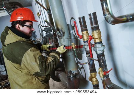 industrial plumber assembling pipes, valves, faucets in water circulation room poster
