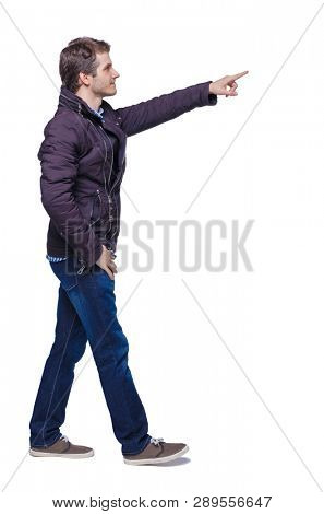 Side view of a man walking with a pointing hand. going  guy showing.   Rear view people collection. Isolated over white background. A young guy in a jacket passes by showing a finger forward.