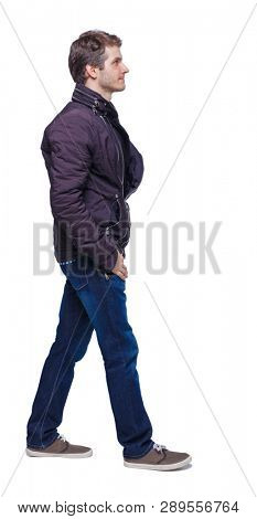 Side view of going handsome man in jeans and jacket. walking young guy . Rear view people collection.  backside view of person. Isolated over white background. A young guy in a jacket passes by.