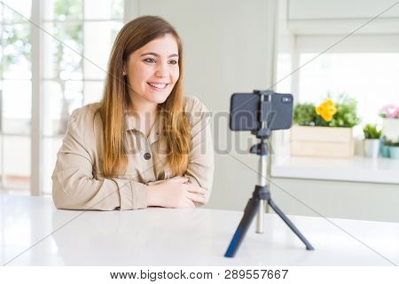 Beautiful young woman doing online video call using smartphone webcam with a happy and cool smile on face. Lucky person. poster