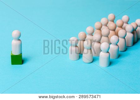 Wooden Figures On A Blue Background. Leader And Team. Business Structure