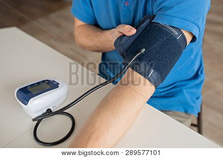 Hypertension Concept. Man Is Measuring Blood Pressure With Monitor In Home. Hands Close-up
