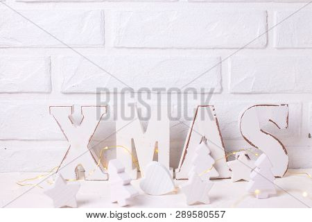 Word Xmas Made From Wooden Letters, Wooden Stars, Hearts And Trees, Fairy Lights  Near By White Bric