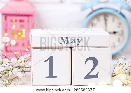 Calendar,  White Flowers, Pink Candleholder With Fairy Lights, Blue Clock On White  Background. Sele