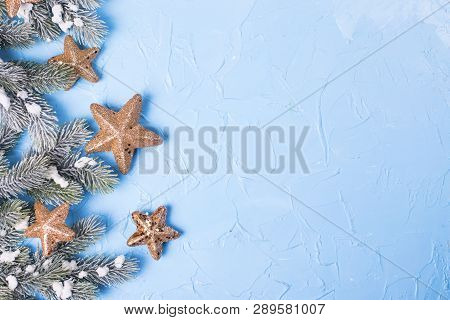 Frame From Branches Fir Tree And Golden Stars  On Blue Textured  Background. Selective Focus. Place