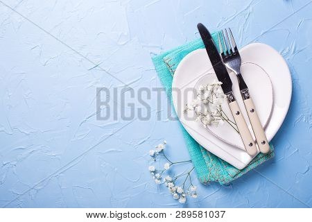 Plates In Form Of Hearts, Napkin, Knife And Fork And  Fresh White Gypsofila  Flowers On Blue Texture