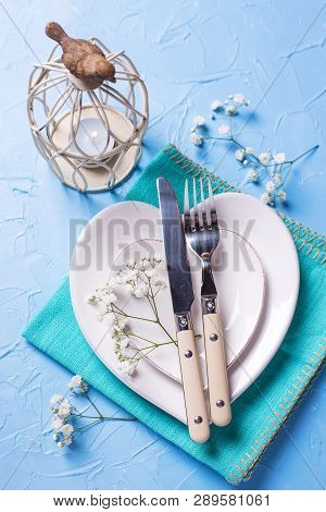 White Plates In Form Of Hearts, Napkin, Knife And Fork And  Fresh White Gypsofila  Flowers On Blue T