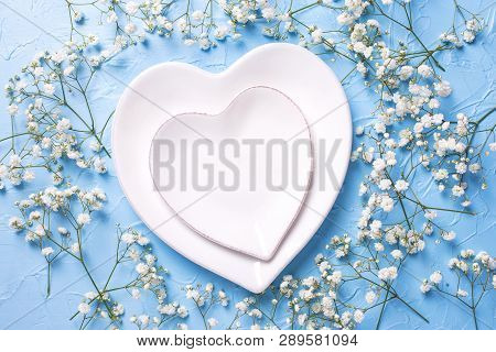 Plates In Form Of Hearts And  Fresh White Gypsofila  Flowers On Blue Textured Background. Top View.
