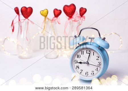 St. Valentine Day Background. Blue Alarm Clock And  Red And Golden Hearts  In Bottles And Fairy Ligh
