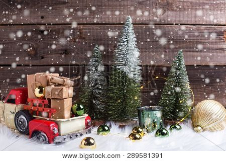 Boxes With Presents In Toy Car, Decorative Fir Trees, Golden And Green Balls And Fairy Lights On Whi