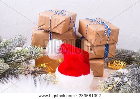 Red Santa Hat, Wrapped Boxes With Presents,  Fir Tree Branches And Fairy Lights On White Textured Ba