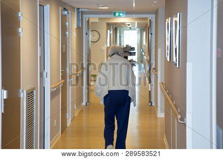 Portrait Of Elderly Woman Walking Down Hallway In Retirement Home Background