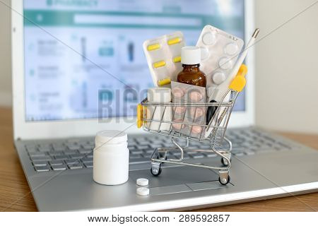 Shopping Cart Toy With Medicaments In Front Of Laptop Screen With Pharmacy Web Site On It. Pills, Bl